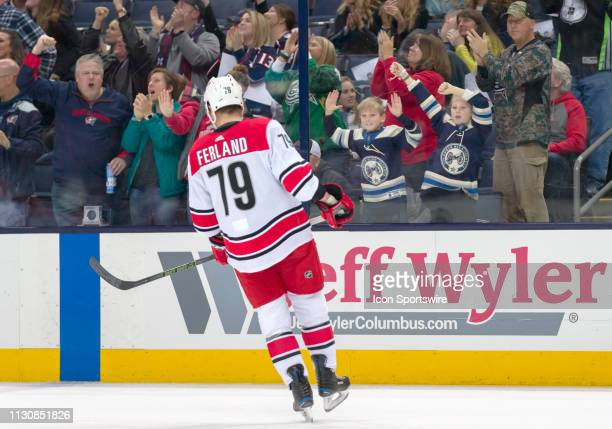 Columbus Blue Jackets fans cheer after a goal as Carolina Hurricanes left wing Micheal Ferland skates the ice in a game between the Columbus Blue...