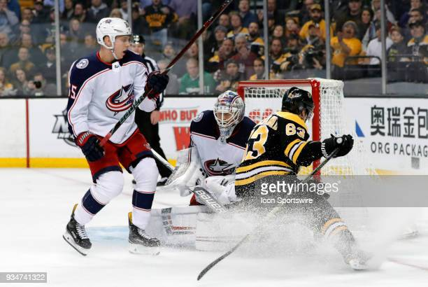 Columbus Blue Jackets goalie Joonas Korpisalo holds onto the puck as Boston Bruins left wing Brad Marchand hits the brakes during a game between the...