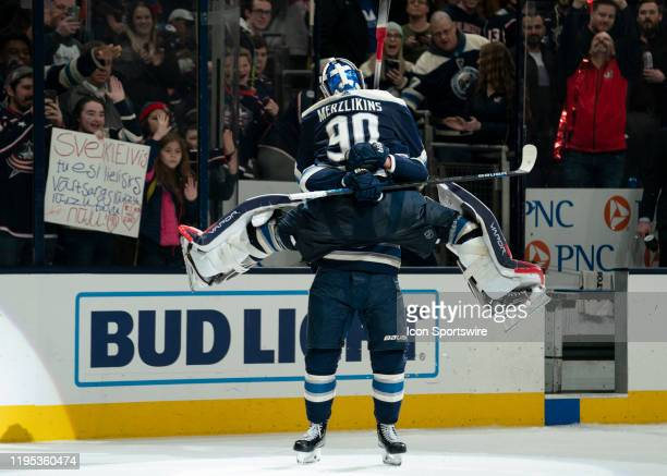 Columbus Blue Jackets goaltender Elvis Merzlikins celebrates a win by jumping into the arms of Columbus Blue Jackets left wing Nick Foligno after the...