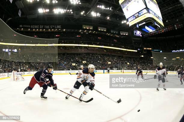 Columbus Blue Jackets left wing Matt Calvert and Edmonton Oilers defenseman Yohann Auvitu sprint for control of the puck during the third period in a...