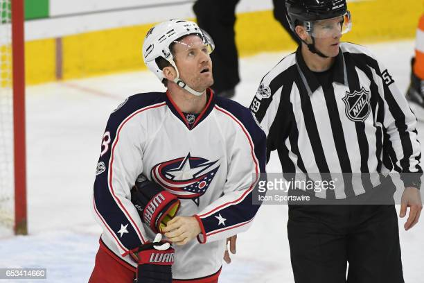 Columbus Blue Jackets Left Wing Scott Hartnell is escorted to the penalty box by linesman Steve Barton during a National Hockey League game between...
