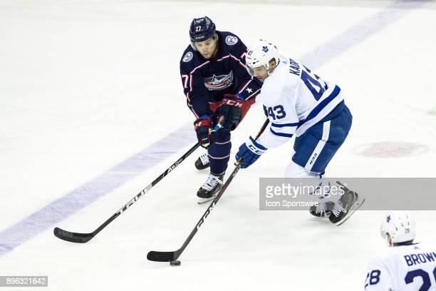 Columbus Blue Jackets right wing Josh Anderson and Toronto Maple Leafs center Nazem Kadri battle for the puck during the first period in a game...