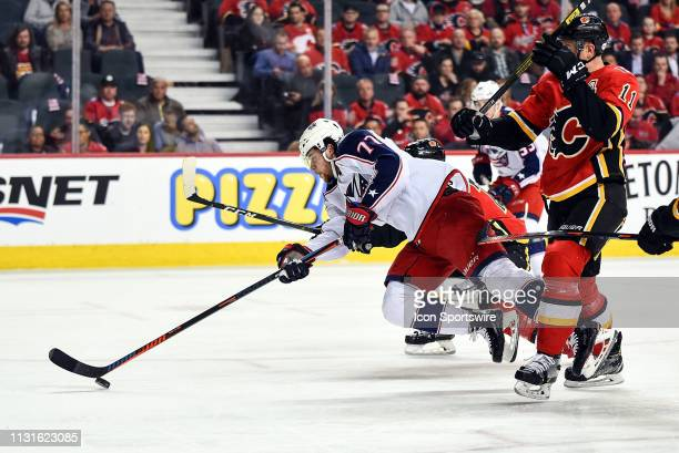 Columbus Blue Jackets Right Wing Josh Anderson attempts a shot on net as falls after being harassed by Calgary Flames players during the first period...