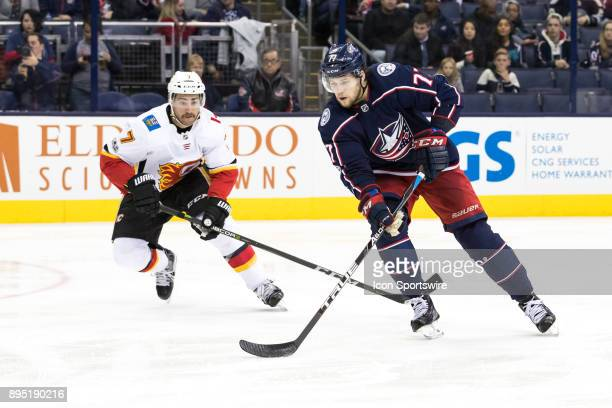 Columbus Blue Jackets right wing Josh Anderson controls the puck while Calgary Flames defenseman TJ Brodie pursues in the third period of a game...