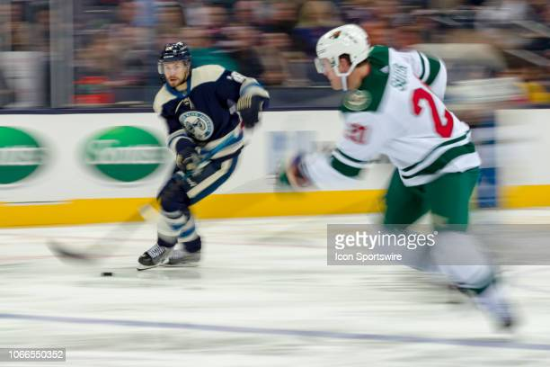 Columbus Blue Jackets right wing Oliver Bjorkstrand looks for an open man as Minnesota Wild center Eric Fehr moves to intercept in a game between the...