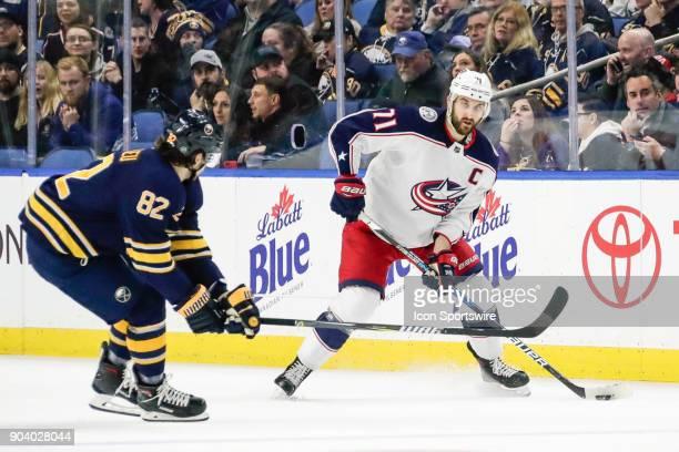 Columbus Blue Jackets Winger Nick Foligno looks to pass as Buffalo Sabres Defenseman Nathan Beaulieu defends during the Columbus Blue Jackets and...