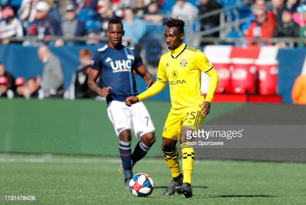 Columbus Crew defender Harrison Afful plays the ball away from New England Revolution forward Cristian Penilla during a match between the New England...