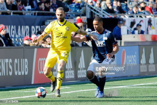 Columbus Crew midfielder Justin Meram fends off New England Revolution defender Brandon Bye during a match between the New England Revolution and...
