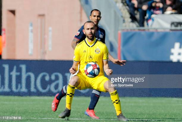 Columbus Crew midfielder Justin Meram traps the ball watched by New England Revolution defender Edgar Castillo during a match between the New England...