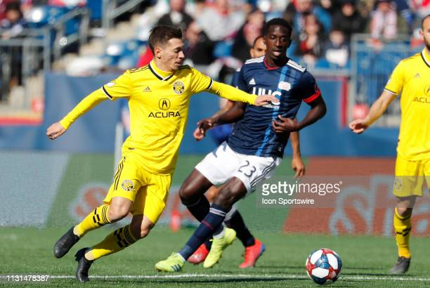 Columbus Crew midfielder Pedro Santos cuts away from New England Revolution midfielder Wilfried Zahibo during a match between the New England...