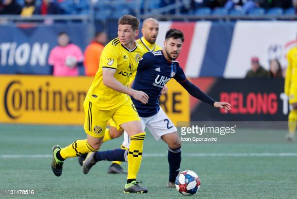 Columbus Crew midfielder Wil Trapp looks for help with New England Revolution forward Carles Gil closing in during a match between the New England...