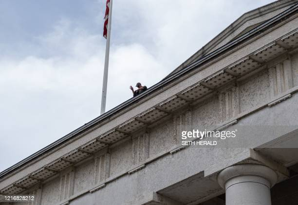 "Columbus Police Department officer waves to protesters as he sits down in solidarity as they chant ""sit with us!"" on the Ohio Statehouse roof in..."