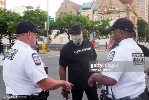 Columbus Police officers speak to a protester as thousands march towards the Statehouse on June 2, 2020 in downtown Columbus, Ohio.. Protesters...