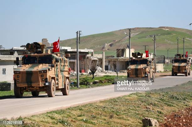 A column of armoured Turkish military vehicles drives on a patrol along a road in the demilitarised zone in the western countryside of Syria's Aleppo...