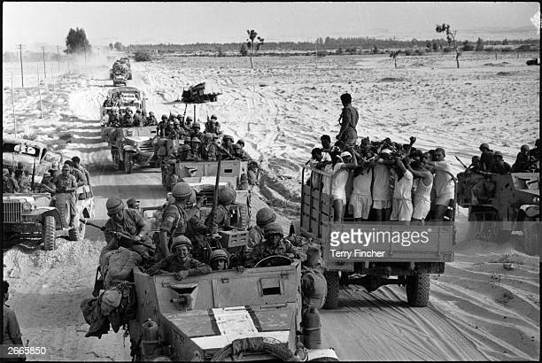 A column of Israeli mechanised infantry moves up to the Suez front as a truck carrying Egyptian prisoners of war in their underwear heads in the...
