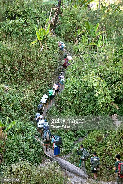 A column of Karen guerillas in charge of security and porters carrying medicines clothes and other material for displaced people start an expedition...