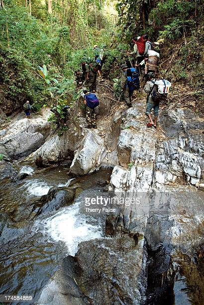 A column of Karen guerillas in charge of security and porters carrying medicines clothes and other material for displaced people walk along a stream...