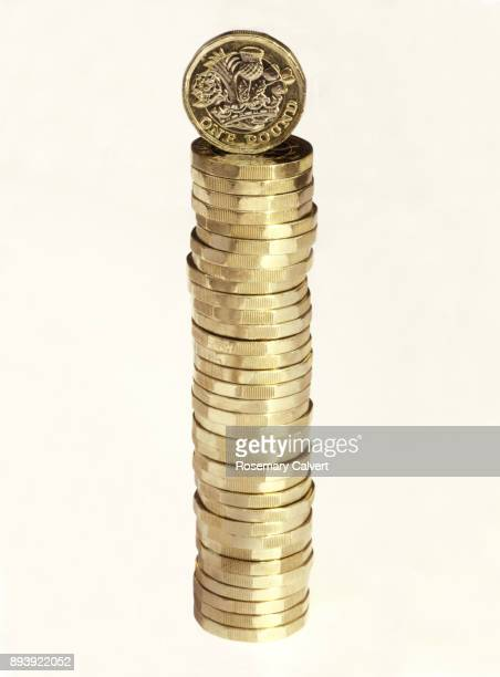 Column of pound coins with one precariously balanced on top