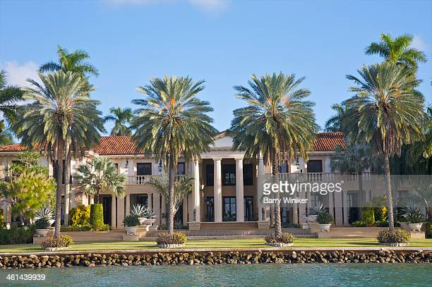 Columned mansion seen through palm trees