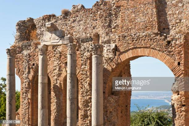 columns and wall inside the greek theatre, and view of golfo di naxos, taormina, sicily, italy - naxos sicily stock pictures, royalty-free photos & images