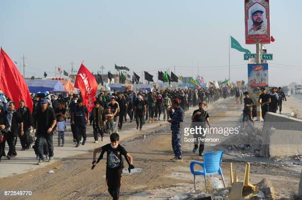 Columns of Shiite pilgrims waving religious flags and banners march 50 miles from Najaf north to the shrine of Imam Hossein to commemorate arbaeen...
