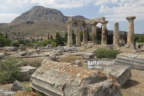 Columns of the former Temple of Apollo stand at the ancient archeological site of Corinth as the ancient fortification of Corinth stands on a hilltop...
