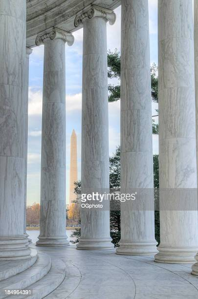 columns of the jefferson memorial framing washington monument - jefferson memorial stock pictures, royalty-free photos & images