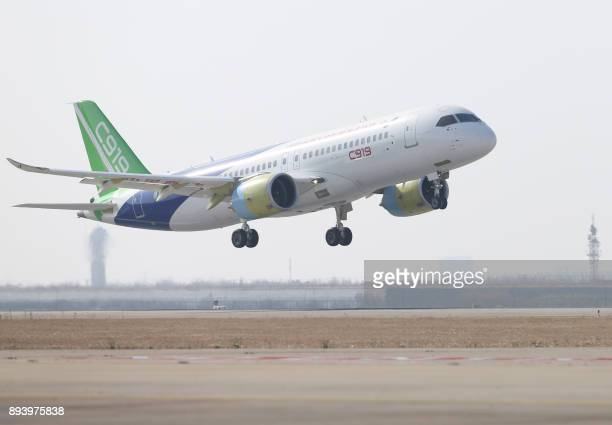 A Comac C919 the China's first mediumhaul passenger jet aircraft takes off from Pudong International Airport in Shanghai on December 17 2017 The...