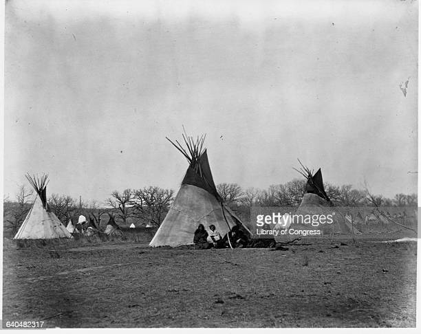 A Comanche Indian family sits outside their teepee in the Iron Mountain's Camp 1873