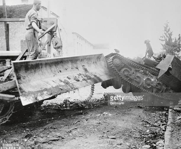 Combat engineers in a bulldozer rapidly clear the roads in St Maire En chaux of Destroyed German Equipment