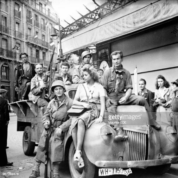 Combattants from the 2nd Armoured Division in waterproofs posing with FFIs and a Parisian woman on a vehicle seized from the Germans in the Gare du...