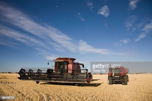 A combine and tractor in a field