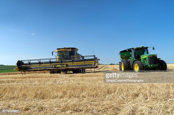 combine and tractor in wheat field - john deere tractor stock photos and pictures