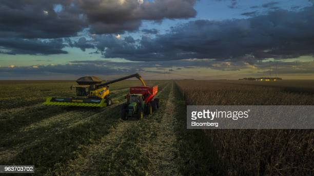 A combine harvester loads corn grain into a tractor at a farm in Rosario Bahia state Brazil on Tuesday May 8 2018 At the end of the last century...