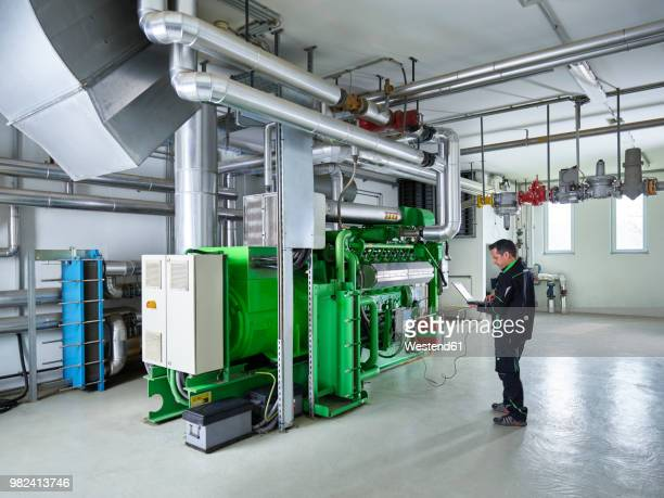 Combined heat and power plant, worker using laptop in front of gas engine