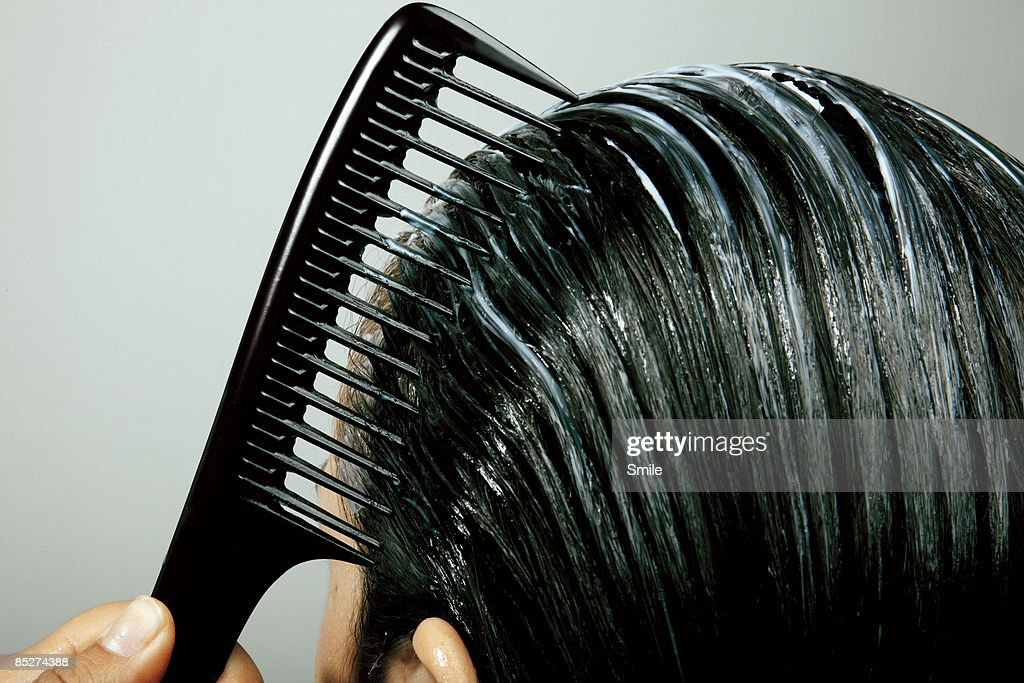 combing conditioner through hair, close up : Stock Photo