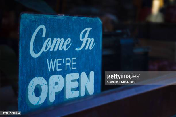 """come in"" ""we're open"" store welcome sign in retail window display - economic stimulus stock pictures, royalty-free photos & images"