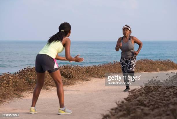 Kommen, können Sie es tun! Ich glaube an dich! Die übergewichtige Frau rennt mit Trainerunterstützung.