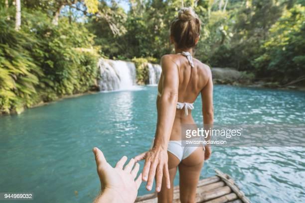 komm mit mir baby, bikini-mädchen, die einladen zum wasserfall beitreten - following stock-fotos und bilder