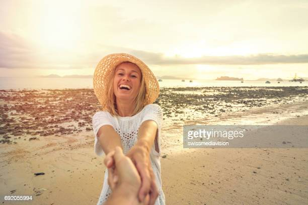 come with me- follow me concept, girl leading boyfriend to beach - following stock pictures, royalty-free photos & images