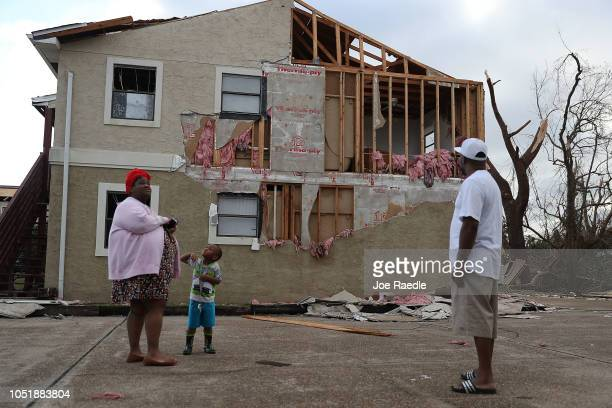 Comeasha Stanley Ramari Stanley and Terrell Atkinson stand near a heavily damaged apartment after Hurricane Michael passed through the area on...