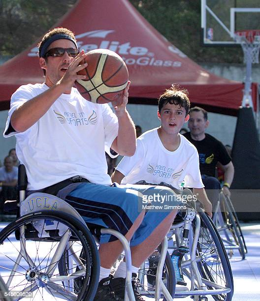 Comedian Adam Sandler and Ezra Frech play in a celebrity wheelchair basketball game during the 2nd Annual Angel City Games at UCLA's Drake Stadium on...