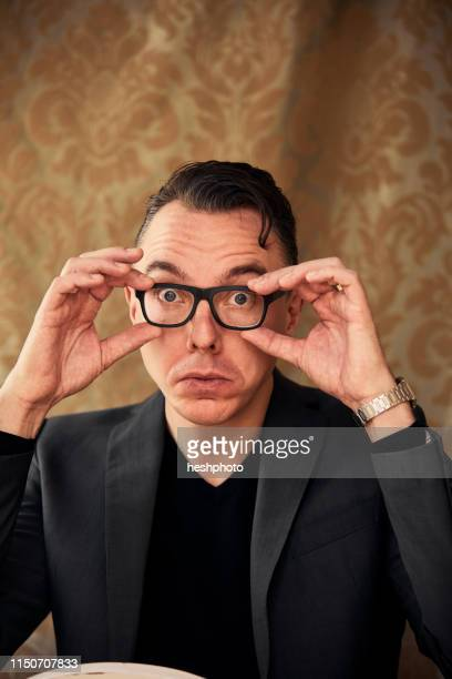 comedian adjusting spectacles for clearer vision - heshphoto fotografías e imágenes de stock