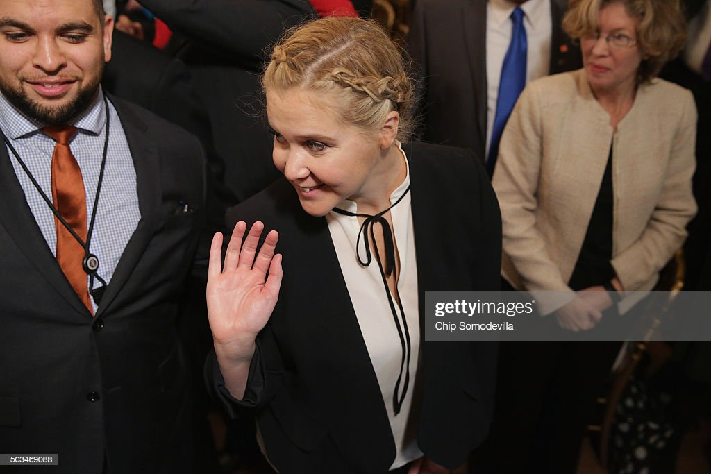 Comedian Amy Schumer (C) waves goodbye after listening to U.S. President Barack Obama deliver remarks about his efforts to increase federal gun control in the East Room of the White House January 5, 2016 in Washington, DC. Without approval from Congress, Obama is sidestepping the legislative process with executive actions to expand background checks for some firearm purchases and step up federal enforcement of existing gun laws.