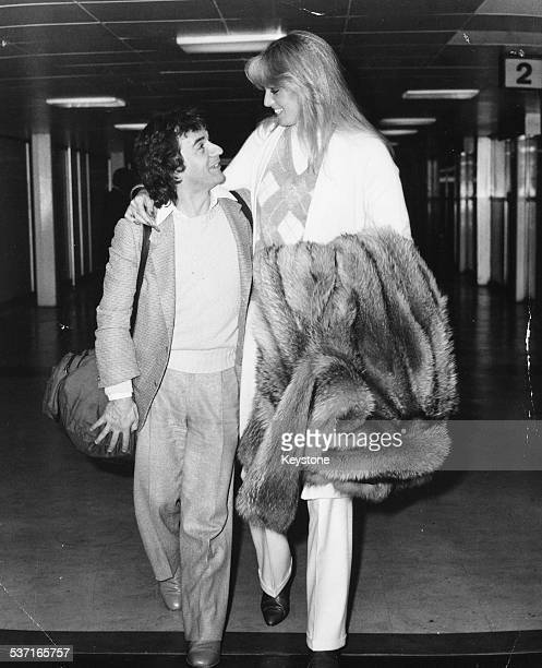 Comedian and actor Dudley Moore with his arm around girlfriend Susan Anton arriving at Heathrow Airport London October 1st 1980