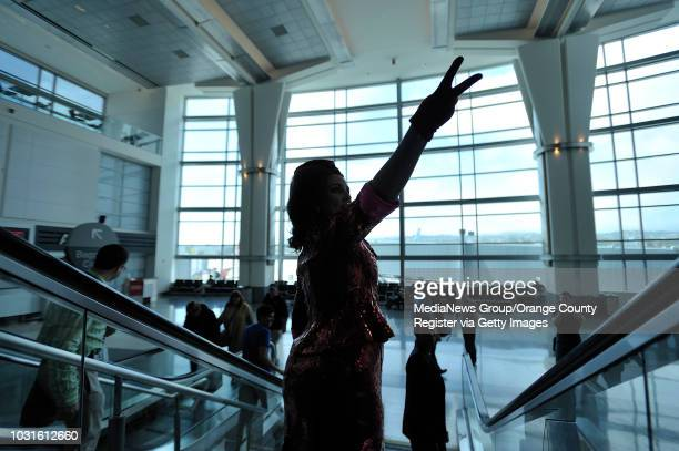 USA Comedian and 'air hostess' Pam Ann gestures to pasengers as she heads towards the gate at San Francisco International Airport before boarding...