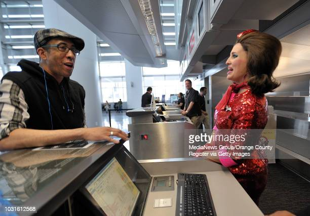 USA Comedian and 'air hostess' Pam Ann welcomes passenger Robert Livingston to the ticket counter before boarding JetBlue's JetPride flight 1969 from...