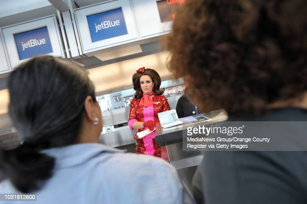 USA Comedian and 'air hostess' Pam Ann welcomes passengers Evangeline Mangosing left and Saudy Sanchez to the ticket counter before boarding...