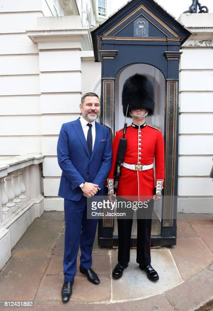 Comedian and author David Walliams poses with a Beefeater palace guardsman during a tea party hosted by Camilla Duchess of Cornwall to celebrate the...