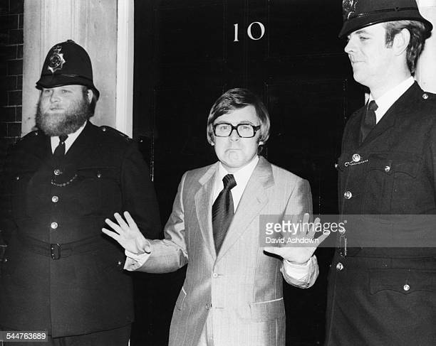 Comedian and impressionist Mike Yarwood joking around with two police officers doing his Callaghan impersonation outside 10 Downing Street London...